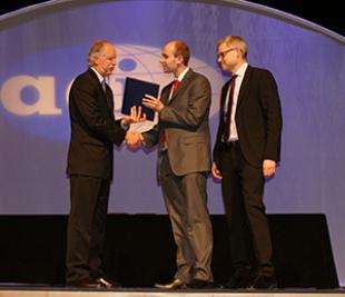 Jason Barrington (centre) and Luke Bisby (right) receive the Award from ACI President Jim White at the ACI Spring Convention in Minneapolis