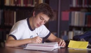 Male Student in white tee shirt studying with book, notepad and pen in a University of Edinburgh library