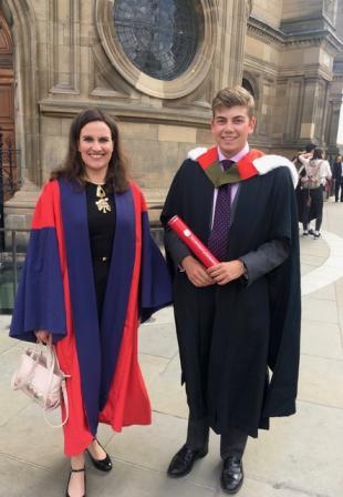 Mr Edward Coleridge with Dr Katherine Dunne on Graduation Day, standing outside McEwan Hall, University of Edinburgh, wearing University robes and smiling