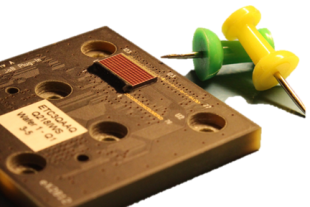 Photograph of the 10 by 5 millilitre SPADnet1 sensor, next to drawing pins to give a sense of scale.