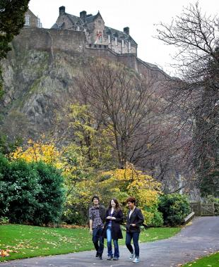 University of Edinburgh students walking through Princes Street Gardens with Edinburgh Castle in background